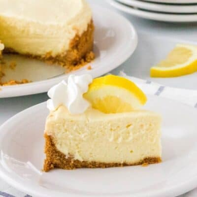 slice of Instant Pot lemon cheesecake on a white plate, with the remaining cheesecake in the background