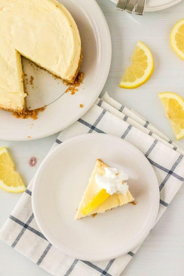 slice of Instant Pot lemon cheesecake on a white plate, atop a blue and white napkin, with the remaining cheesecake behind it and lemon garnishes surrounding the plate.