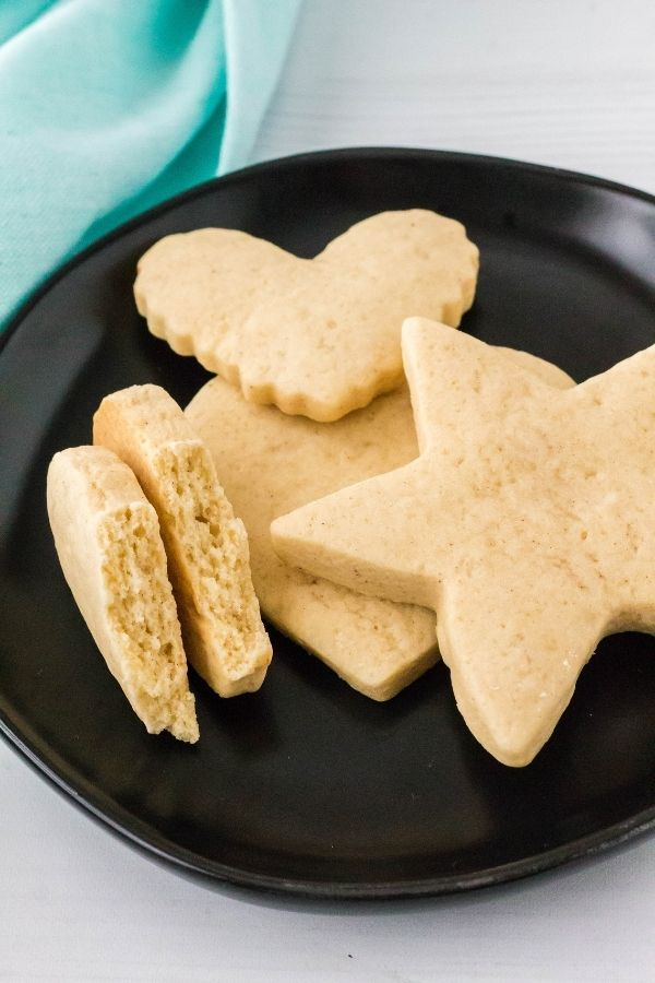 Italian sour cream cookies that have been cut into shapes, served on a black plate