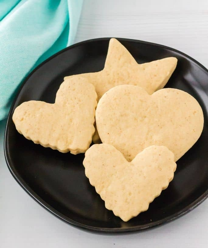 sour cream cutout cookies on a black plate
