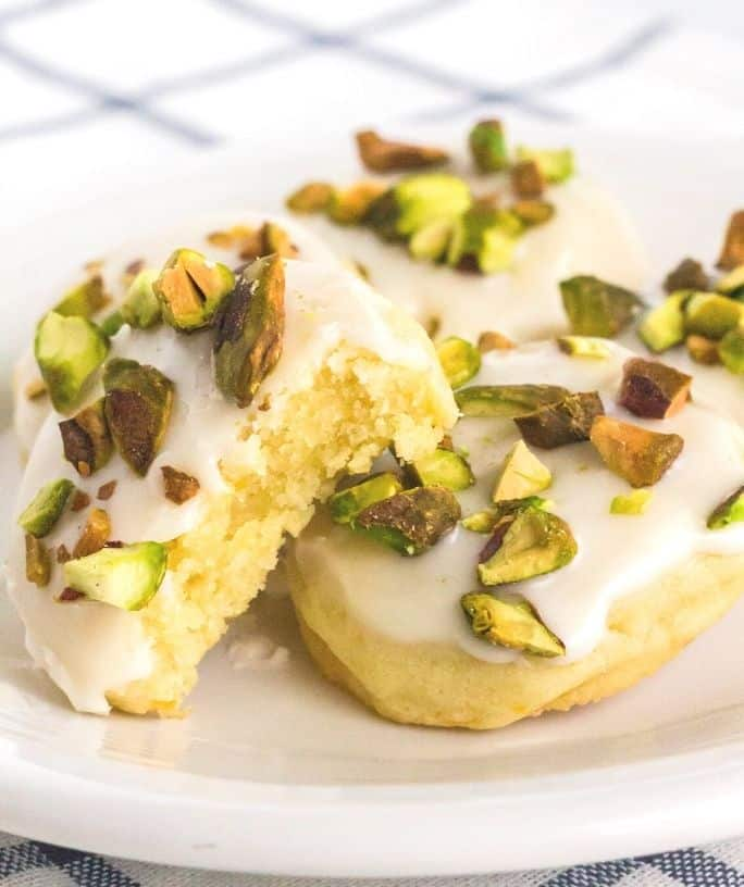 a few lemon pistachio cookies on a white plate, with a bite taken out of one.