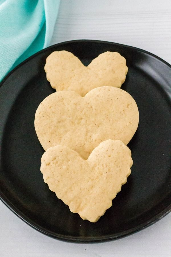 three heart-shaped sour cream cookie cutouts on a black plate