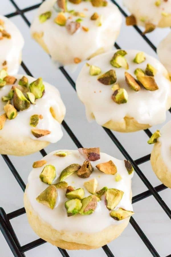 freshly iced lemon pistachio cookies on a cooling rack