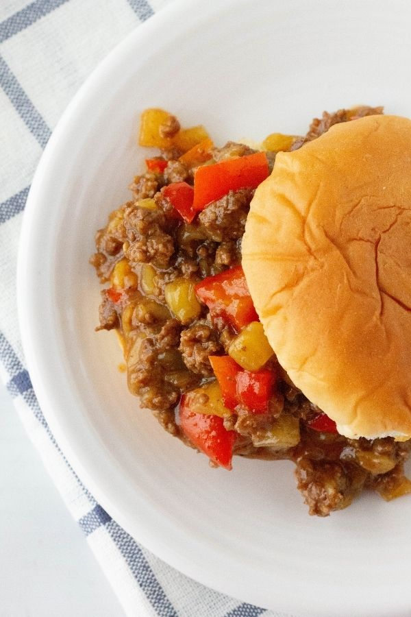 overhead view of a pressure cooker Hawaiian Sloppy Joe sandwich on a white plate next to a blue and white cloth napkin
