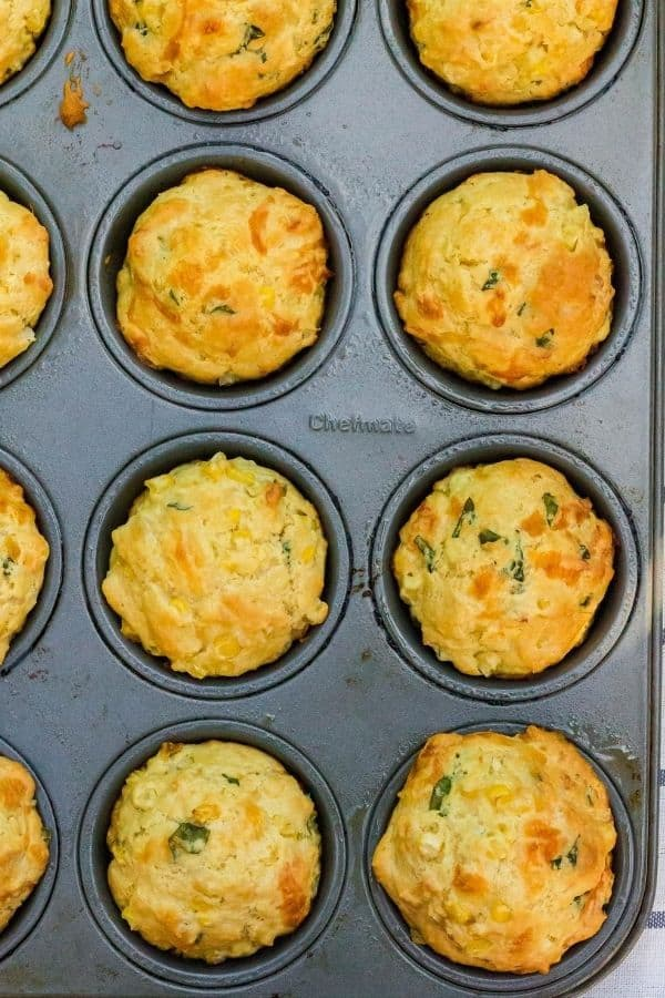 muffin pan filled with freshly baked cheesy corn and basil muffins
