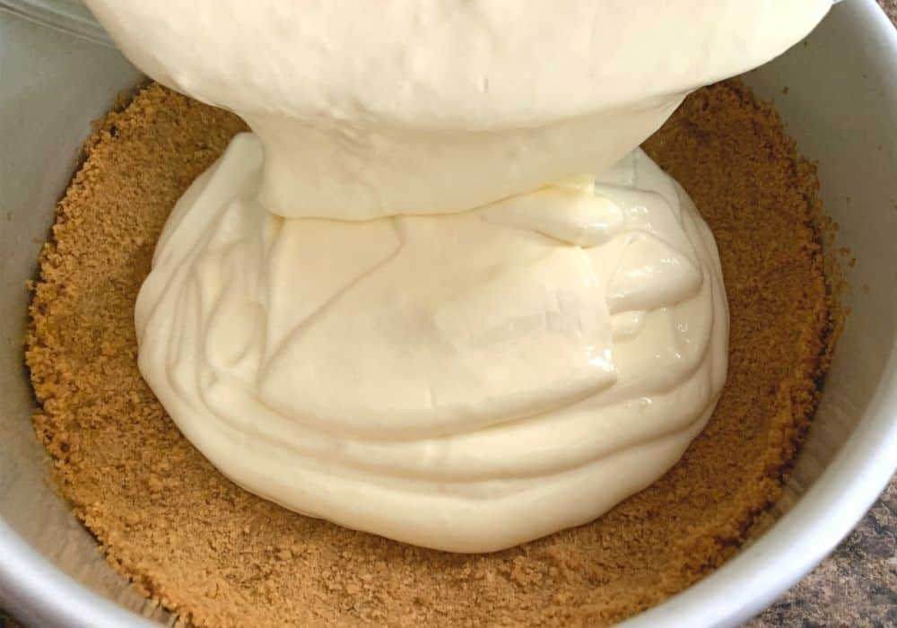 lemon cheesecake batter being poured into prepared crust