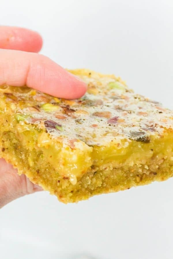 a woman's fingers holding a lemon pistachio bar.
