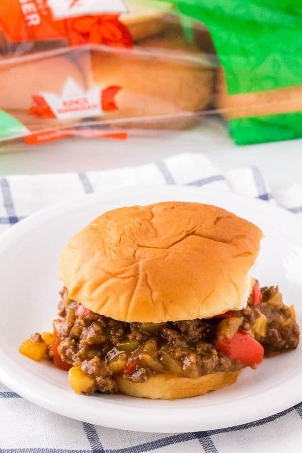 Instant Pot Hawaiian Sloppy Joes sandwich on a white plate in front of a Kings Hawaiian Sweet Rolls package