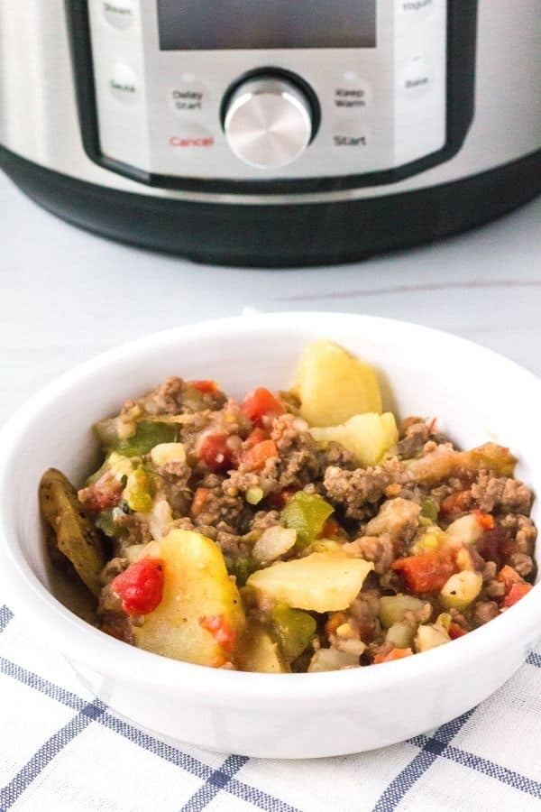 Dolly Parton's 5 Layer Dinner served in a white bowl in front of an Instant Pot pressure cooker