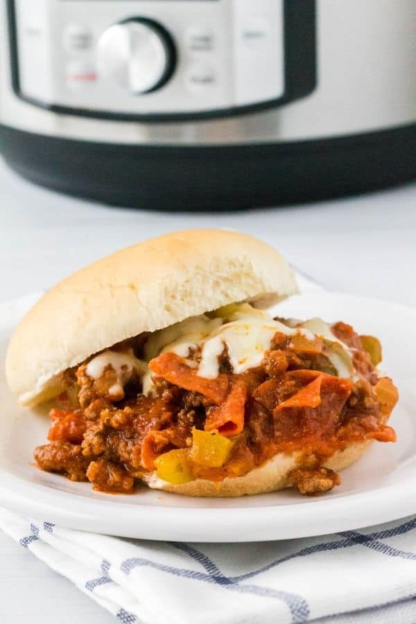 a pizza burger sandwich on a white plate in front of an instant pot pressure cooker