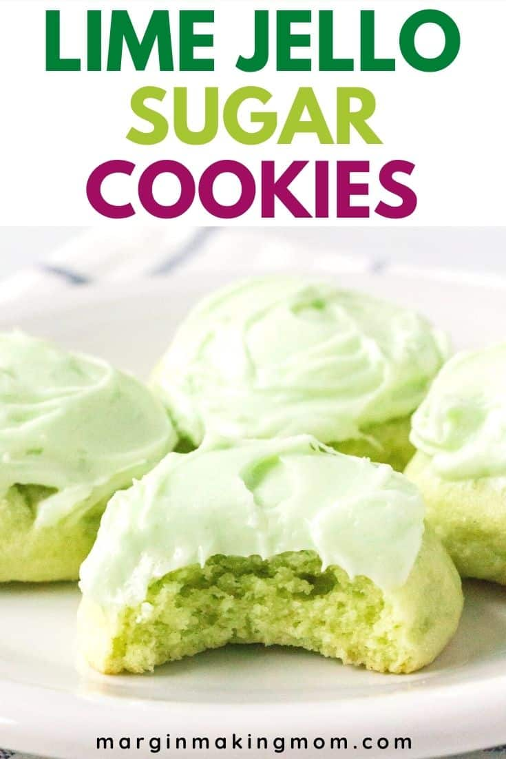four frosted lime jello sugar cookies on a white plate, with a bite taken out of the front cookie to show the soft interior