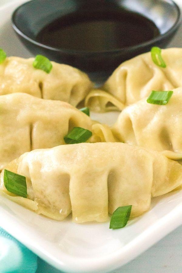 Instant Pot frozen dumplings, freshly steamed, served on a white plate.