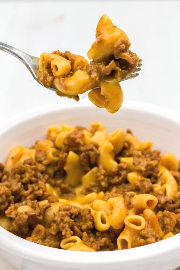 a fork lifting a bite of Instant Pot Hamburger Helper out of a white bowl