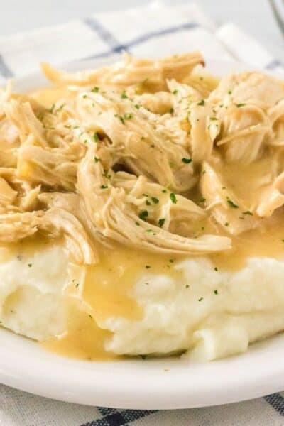 a bed of mashed potatoes covered with instant pot chicken and gravy