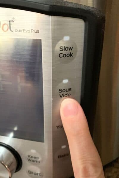 a finger pointing to the sous vide button on an Instant Pot