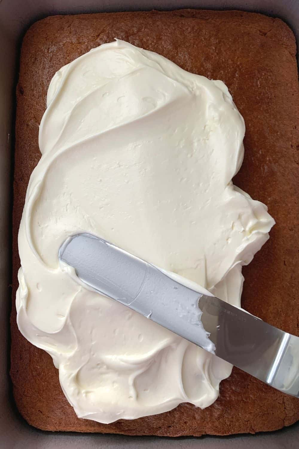 an offset spatula spreading fluffy cream cheese frosting on a baked tomato soup cake