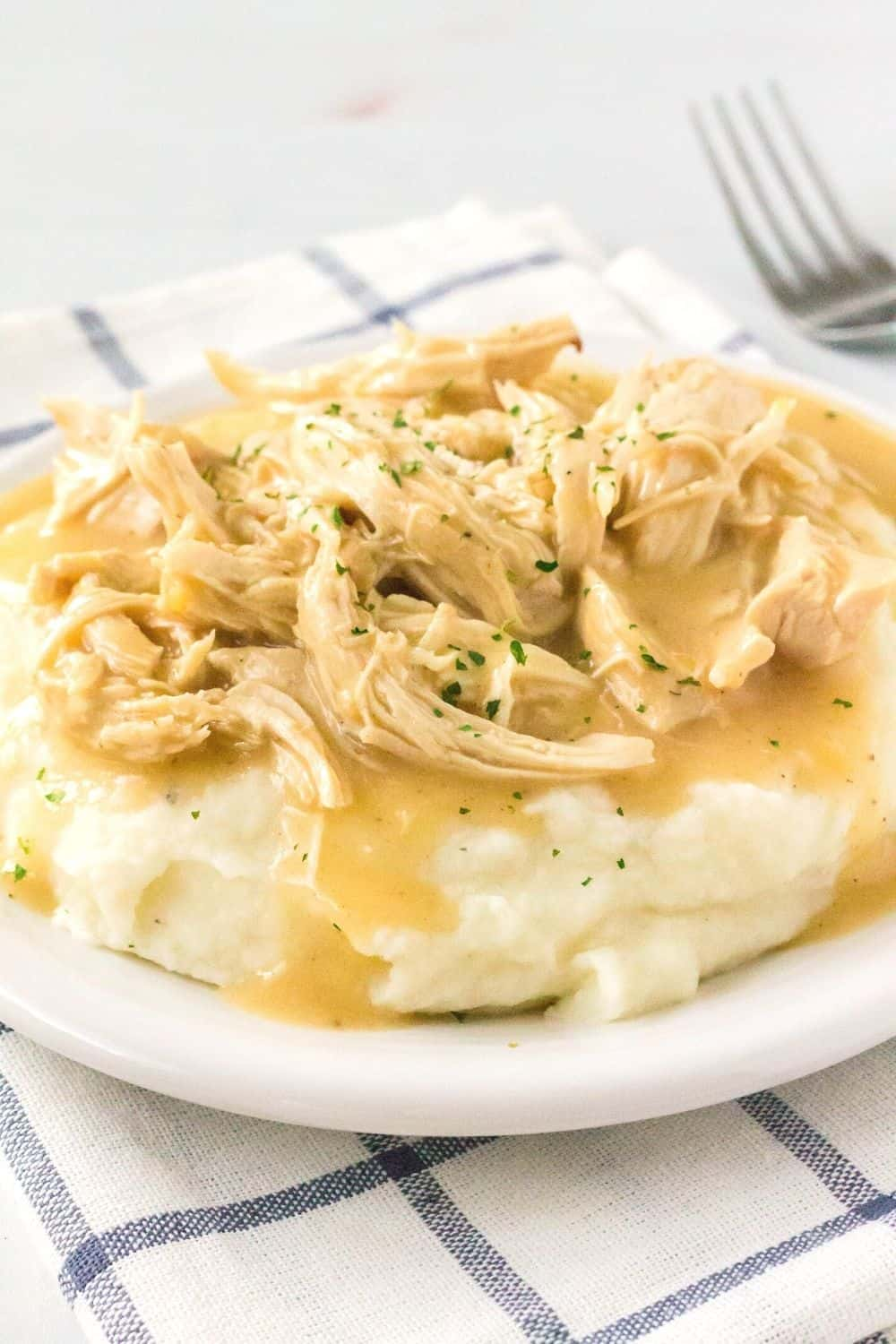 pressure cooker chicken and gravy served over mashed potatoes on a white plate, atop a blue and white napkin