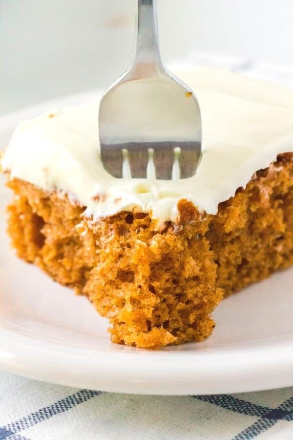 side view of the corner of a slice of tomato soup sheet cake, with a fork taking a bite out of the cake