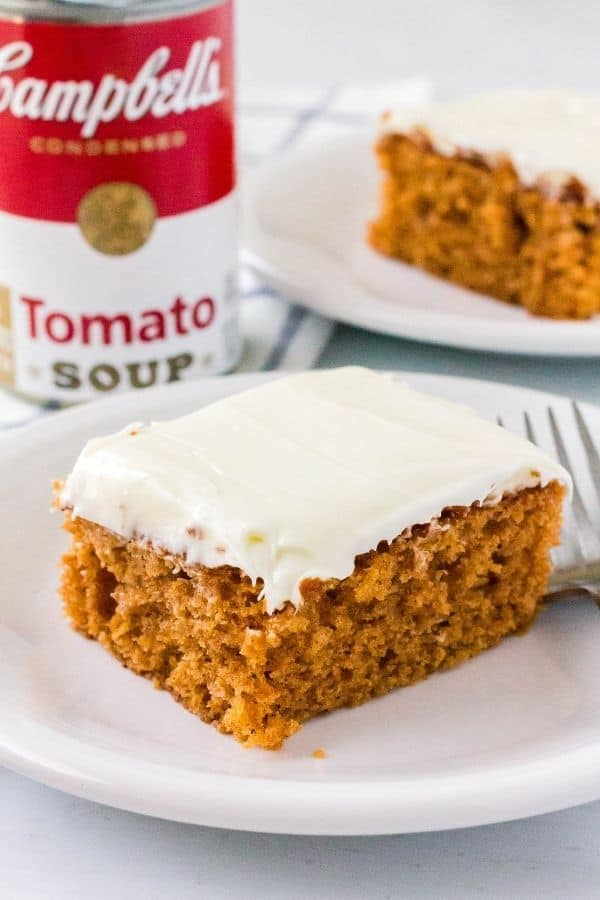 a slice of spice cake made with condensed tomato soup, topped with frosting, on a white plate
