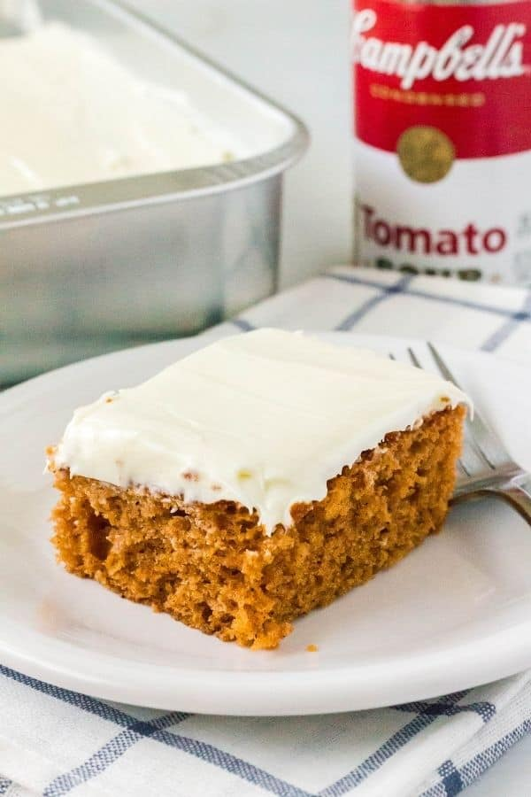 spice cake made with tomato soup, topped with cream cheese frosting, and served on a white plate
