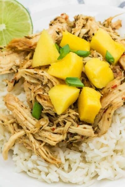 a plate of Instant Pot jerk chicken served over rice and topped with mango and green onions