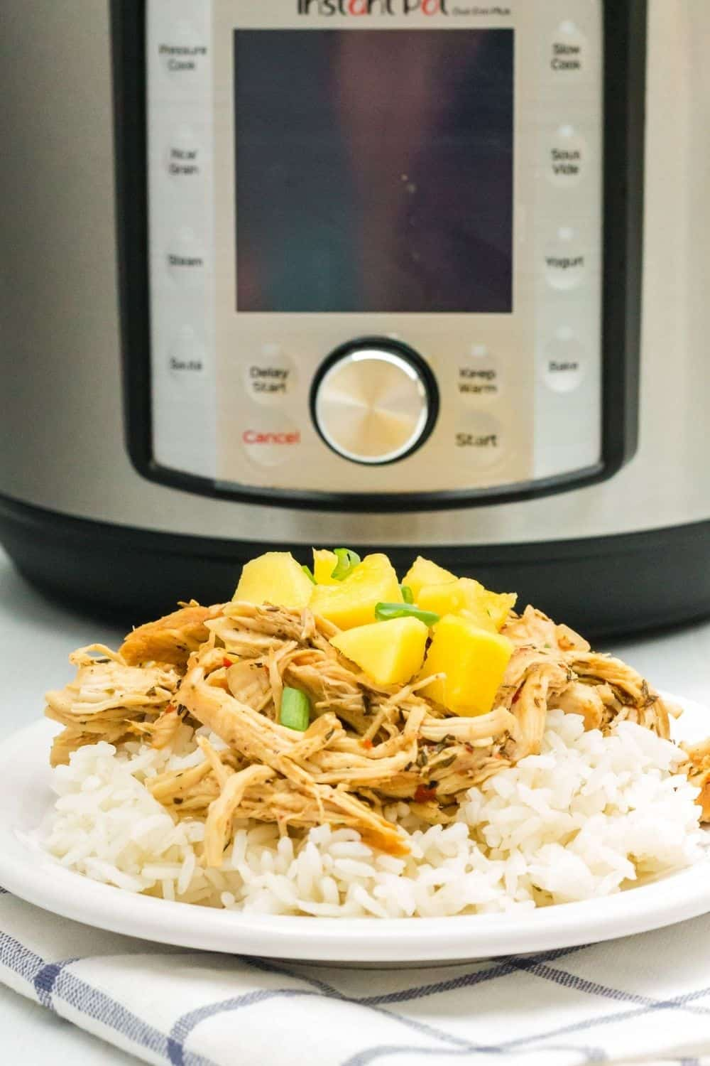 Instant Pot jerk chicken served over rice on a white plate in the foreground, with an Instant Pot pressure cooker in the background