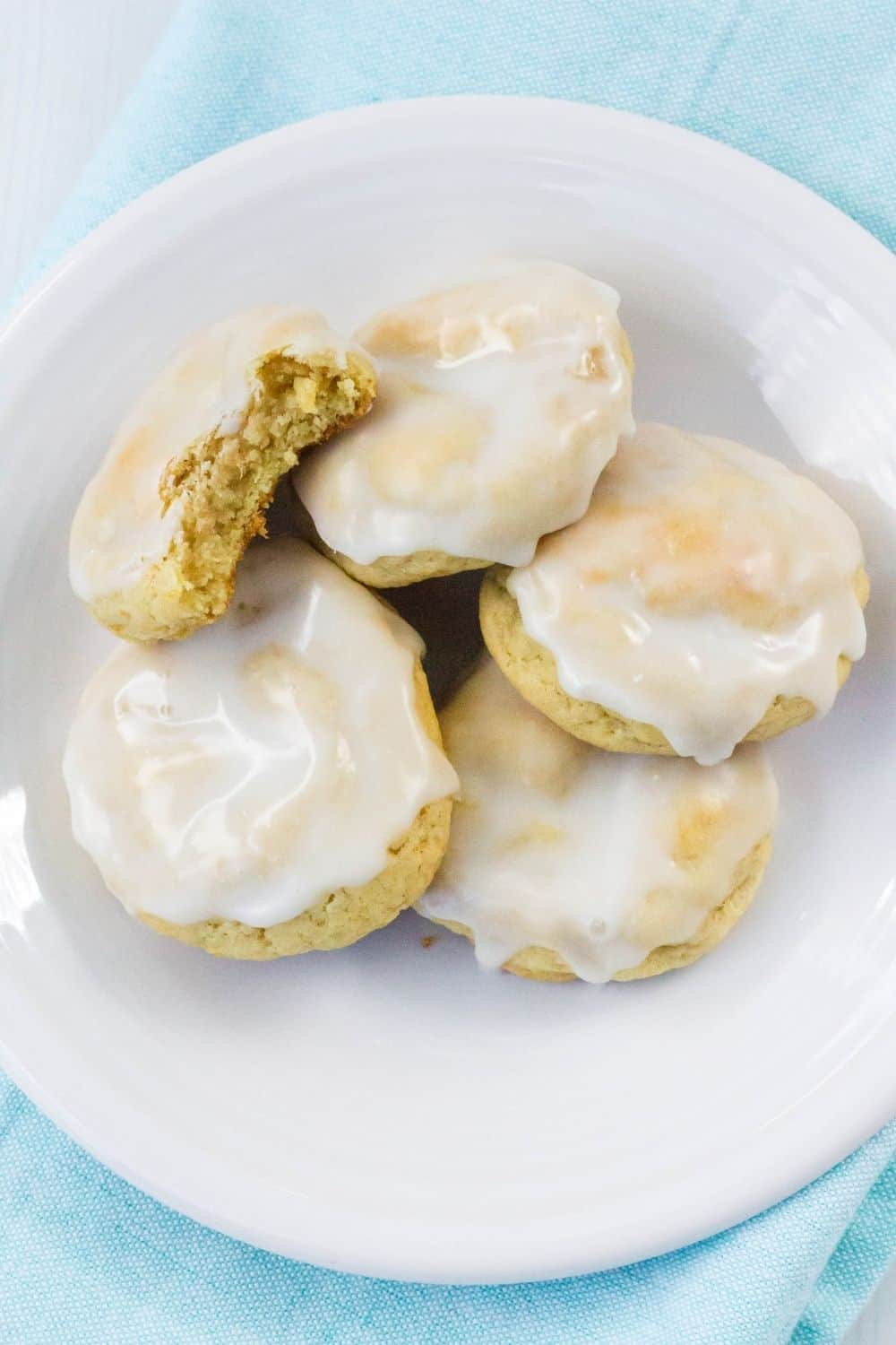 Five iced Hawaiian pineapple cookies on a white plate. One cookie has had a bite taken out of it.