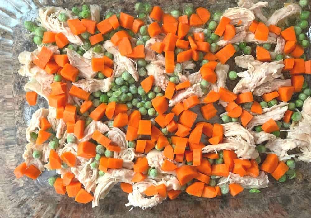 chicken, carrots, and peas on top of melted butter in a baking dish