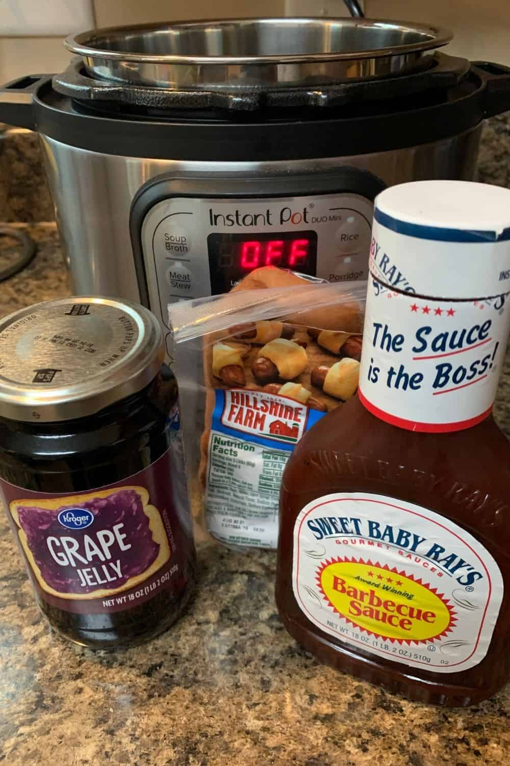 a jar of grape jelly, a bottle of bbq sauce, and a package of Hillshire Farm cocktail sausages in front of an Instant Pot
