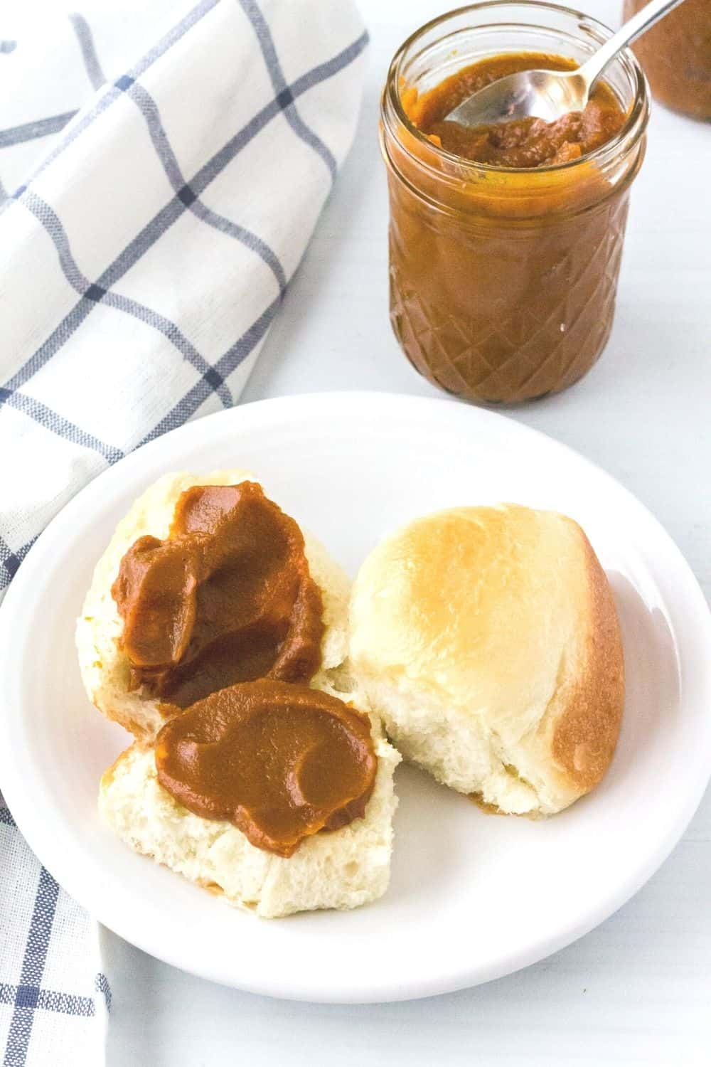 pressure cooker pumpkin butter spread on a halved dinner roll and served on a white plate, with the jar of pumpkin butter in the background.