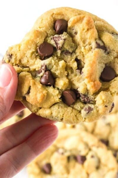 a woman's hand holds a chocolate chip cookie made with no brown sugar