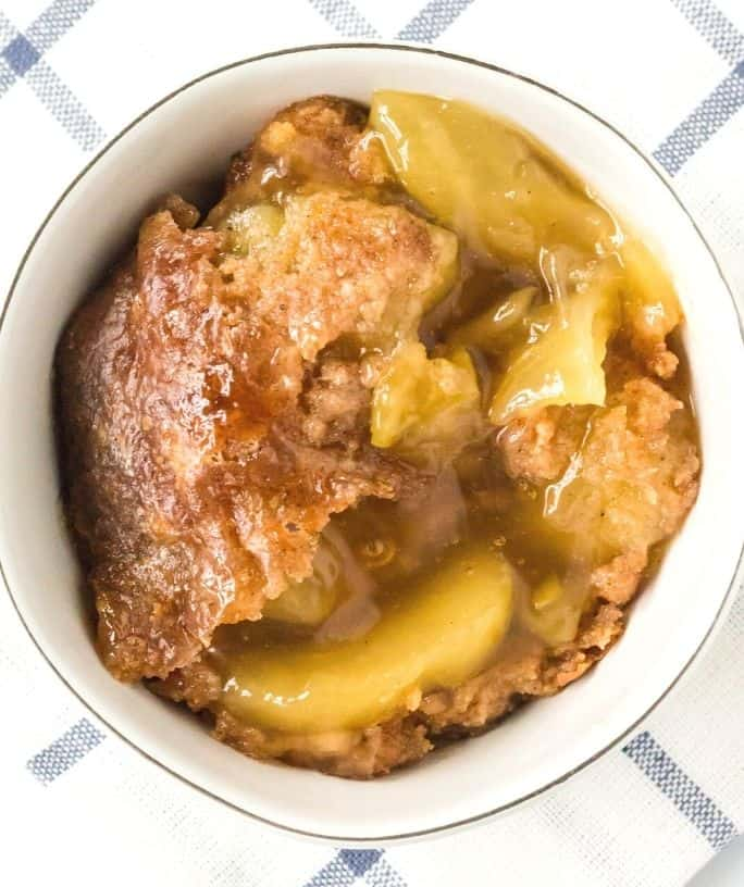 overhead view of a white bowl with a helping of Instant Pot apple dump cake in it