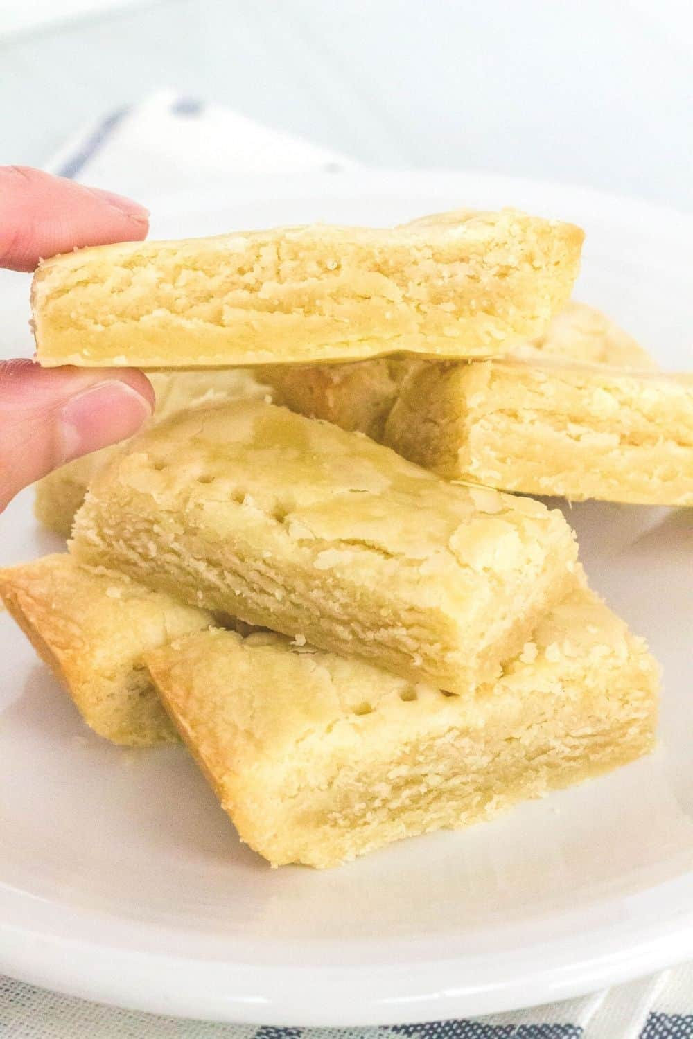a woman's fingers lift a scottish shortbread cookie from a pile of cookies served on a white plate