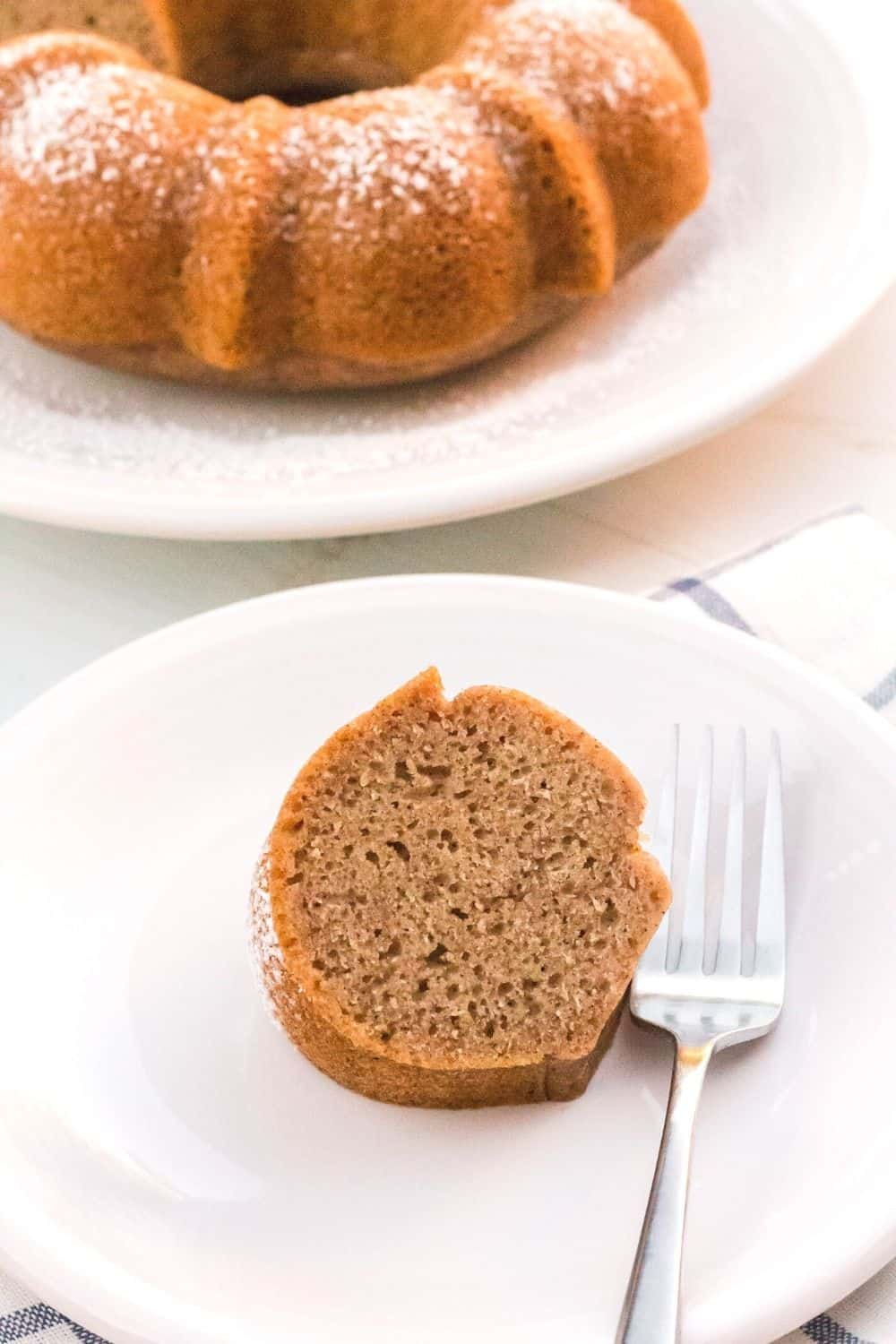 Slice of Instant Pot applesauce bundt cake on a white plate with the remaining cake in the background