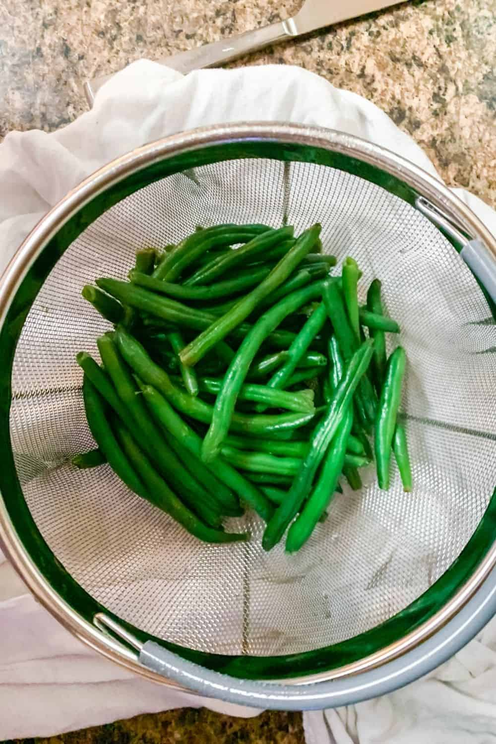 freshly cooked green beans in a steamer basket on a white kitchen towel