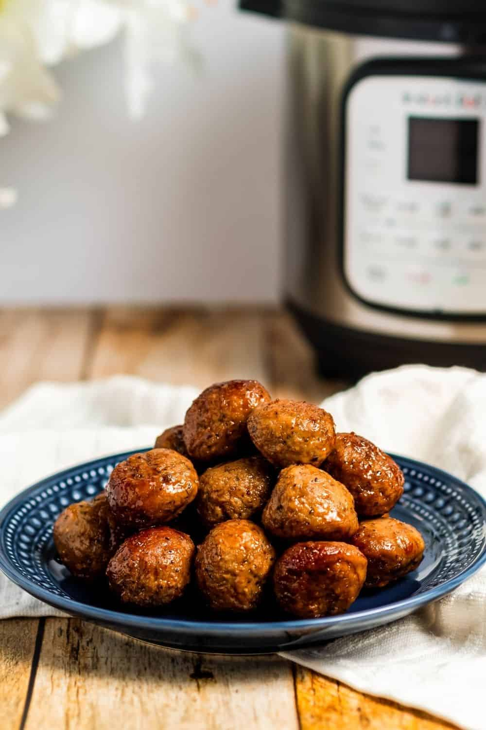 Side view of Instant Pot cocktail meatballs on a blue plate in front of an Instant Pot pressure cooker