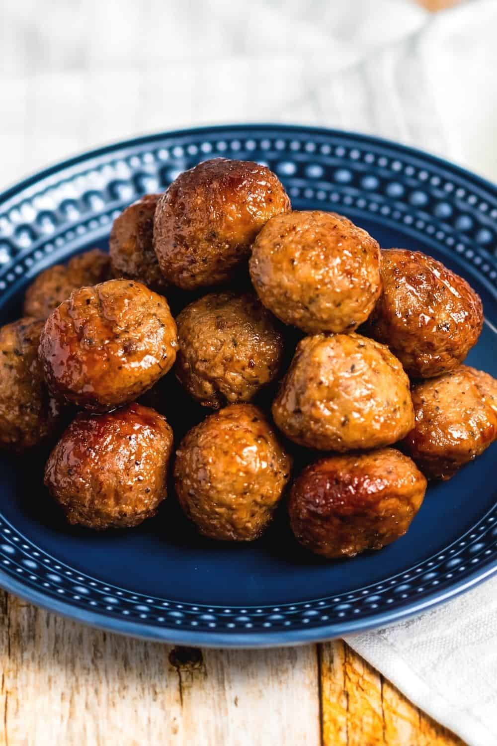 close-up view of Instant Pot grape jelly meatballs on a blue plate