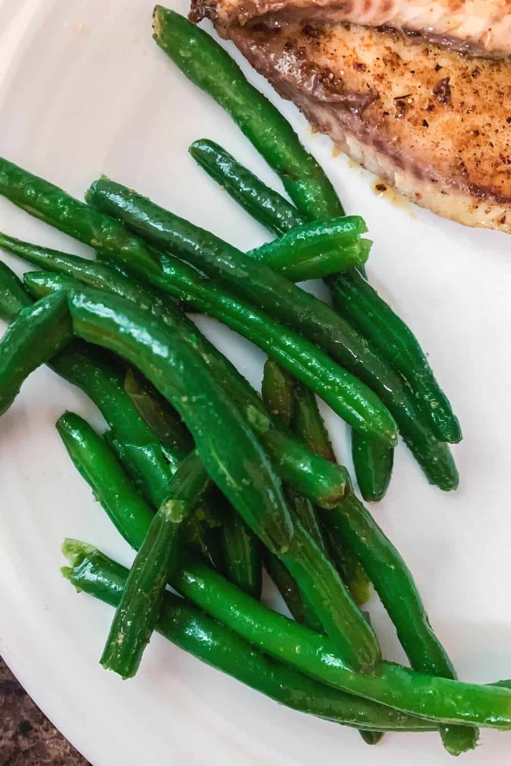 pressure cooker steamed green beans on a white plate next to cooked fish