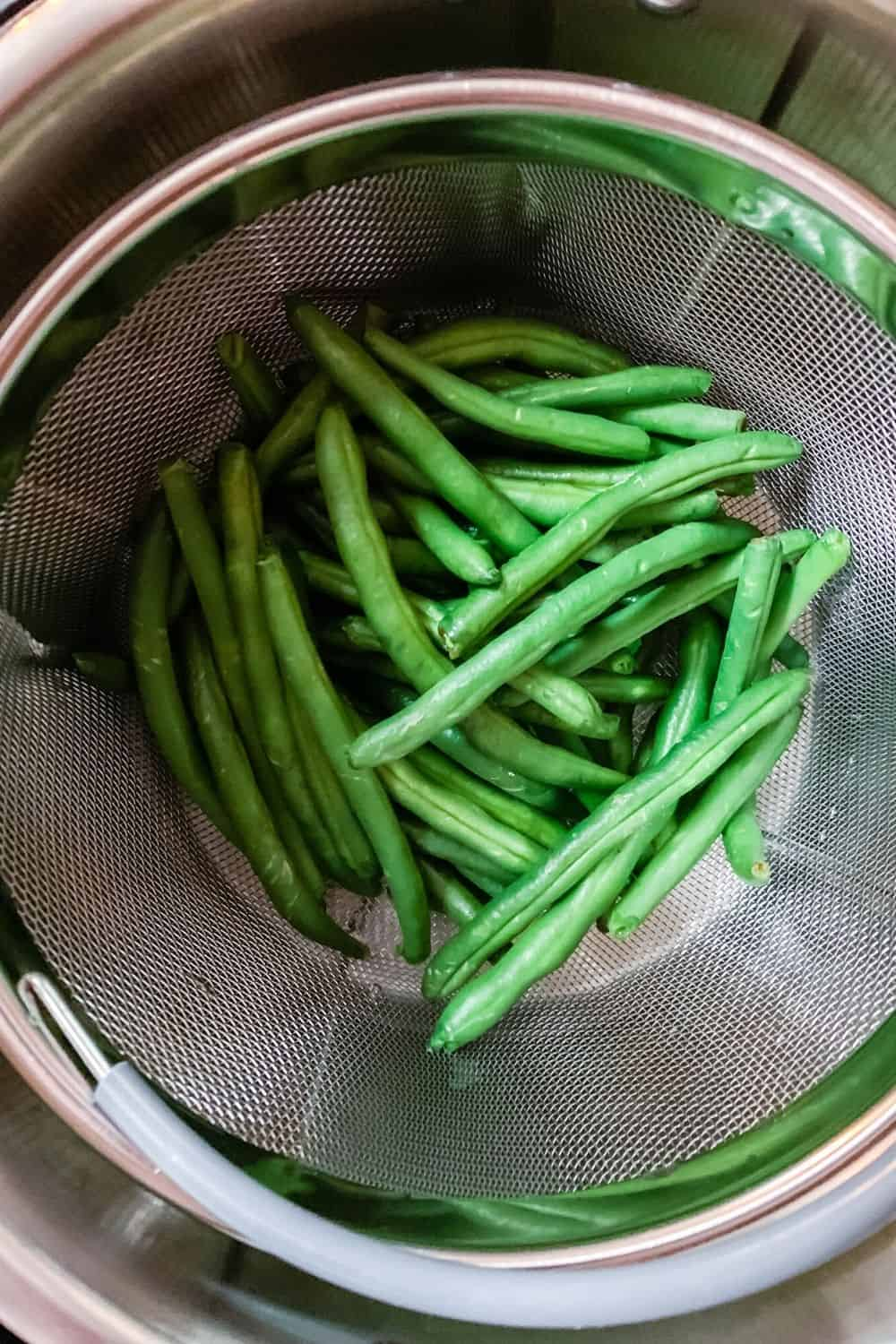 fresh green beans in a steamer basket in the Instant Pot